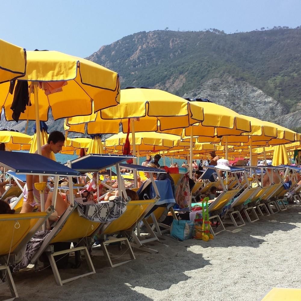Yellow umbrellas line Monterosso al Mare, Italy.